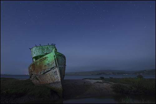 An old boat is silhouetted against the starry night sky, Point Reyes National Seashore, California (by Amigo!)