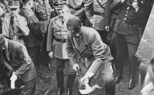 Adolf Hitler wields an axe at a groundbreaking ceremony.