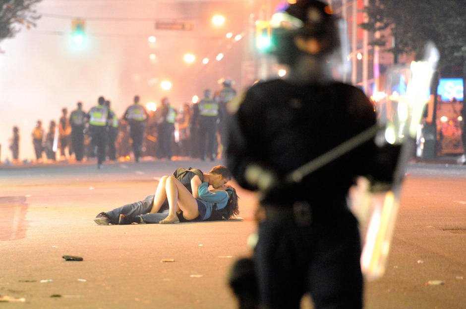 Photos: Riots, fire, destruction after Vancouver's loss Riot police walk the street as a couple kiss on June 15, 2011 in Vancouver, as the city broke out in riots, following the Vancouver Canucks loss in game seven of the Stanley Cup Finals. (Rich Lam/Getty Images)