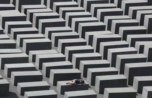 A girl rests on a concrete column of the Holocaust memorial in Berlin, June 17, 2011. The memorial to the murdered Jews of Europe consists of 2,711 charcoal-grey rectangular pillars, which rise from the ground and form a tight grid through which visitors can wander.  (REUTERS/Tobias Schwarz)