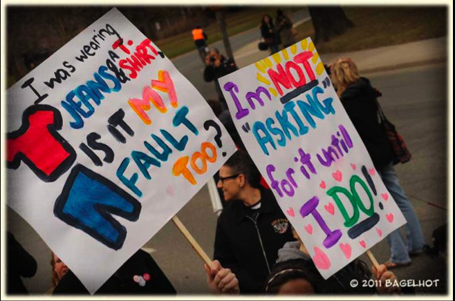 """I was wearing jeans and t-shirt, is it my fault too?""SlutWalk Toronto 2011. My sign. I had mixed feelings about holding my sign at the SlutWalk. It was the first time I really identified myself as a survivor, because for months I was in denial about being raped in the first place. I posted a photo of my sign on the SlutWalk facebook site before the walk, and I had someone message me telling me that my sign hit home with them, and if they could use the same sort of sign too. If you google SlutWalk, guaranteed that her photograph will flood the results. Having someone else there with a similar sign helped. So did meeting P. Her sign said ""Boxing Day 1985. 14 years old. Bundled in layers. How did I deserve it?"" I wanted to cry as soon as I saw her. She came up to me and gave me a hug. It was the best hug I've ever had. Her hug was the first one I received that day, but it wasn't the last. Words of encouragement from random strangers included 'it wasn't your fault,' and 'you're so brave.' After a while, I started to believe it. And I held my sign high and I can honestly say that that day was the first day I was okay about what happened. After that, I started to move on."