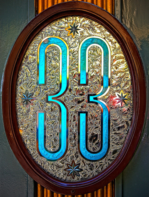 "Club 33 is a secret private club maintained in New Orleans Square in Disneyland. The entrance to the club is next to the Blue Bayou Restaurant and is rather unassuming, save for the ornately decorated plaque with the number ""33"" on it at the doorway. Only members to the club are allowed access to the restaurant, which boasts a wine list including vintages priced at $1,000+. To get to the restaurant, members can take a lift that is an exact replica to the millimeter of a lift Walt Disney fell in love with while in Paris, or they can take the staircase that wraps around the lift. The restaurant has two rooms: the Trophy Room, and the Main Dining Room, and both are filled with props from classic Disney movies. Hanging on the walls are original hand-painted animation cells from Fantasia, as well as butterflies pinned under glass. The balcony of the restaurant overlooks the Rivers of America, providing excellent viewing for shows like Fantasmic! that take place on the water. Members get free access to the park as well as valet parking to the entire Disney resort in California. They are also allowed early admission into the park several days out of the week. Six Fastpasses per day are provided to each member in the party of a club member that are usable with any ride that has the Fastpass option. Members are also allowed access to the presidential caboose car on the Disneyland Railroad, the Lilly Belle. The current waiting list to get into the club is 14 years long, and it is currently closed to new admissions. Individuals pay an initiation fee of $10,450, and a subsequent annual fee of about $3,275. Club 33 only allows 487 members to be apart of the club at any given time. There is a Club 33 in Tokyo Disneyland, however, members of Disneyland's Club 33 do not get reciprocal privileges in Tokyo."