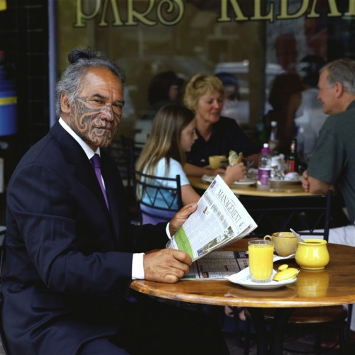 littleaubergine:   An older Maori man wearing a business suit with a purple tie has his long hair up and has traditional facial tattoos covering from his temples down.