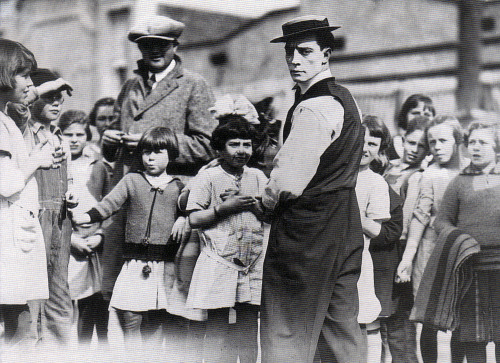 Buster greats some of his young fans while on location, c. 1921. Eddie Cline is the man wearing the cap.