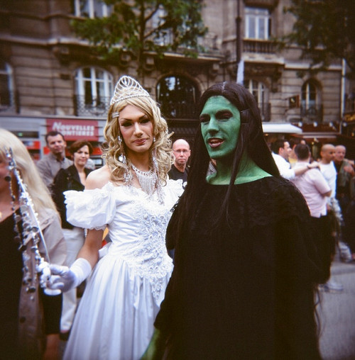 [Drag Queens dressed (presumably) as Elphaba and Glinda from Wicked, photographed on a Paris street]