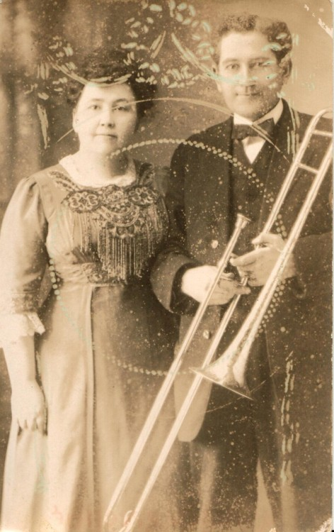 Postcard of an unidentified woman and man with a trombone, featuring some sort of pretty pattern! I have no idea what that could be from.