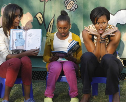 "washingtonpoststyle:  Michelle Obama and daughters Sasha (center) and Malia take turns reading from ""The Cat in the Hat"" during their visit to the Emthonjeni Community Center in Johannesburg today. Video Photo by Charles Dharapak (AP)"