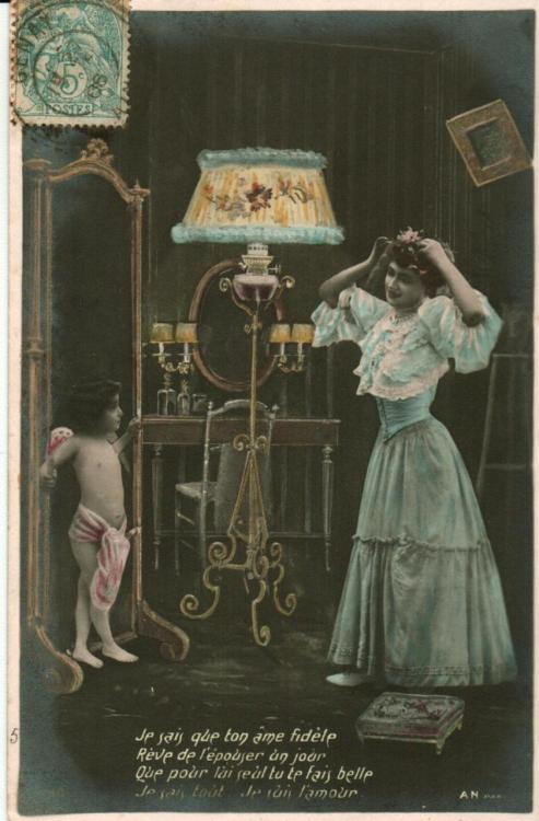 "A hand-colored French postcard, postmarked 1906. A (rather poor) translation of the cupid's French caption is: ""I know that your faithful soulDreams of one day getting marriedFor him alone you will make yourself beautifulI know all   I am love"""