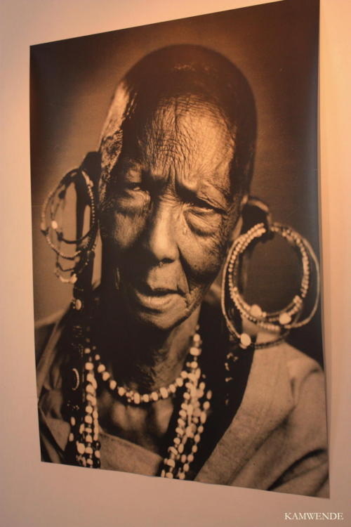 "kamwende:  Portrait of a Kikuyu Lady from the ""Room Uzee na Busara - The Sages, Old Age and the Eternal""   In early 2010, I attended the PIGAPICHA exhibition in Nairobi which celebrated ""A Century of Portrait Photography in Nairobi."" This photo is from the Sages room and part of the room's description reads ""As Kenya forged its identity as a nation, its men and women sought new definitions of themselves. Commercial photo studios became the much desired spaces for expressions of ""Self""."" One thing about the exhibition was the notable loss of information regarding the individuals in the photos as well as the photographers. At best, we only know the studio where some were taken. Exhibition description: ""To be photographed was a part of day-to-day life in Nairobi, whether it was in a photo studio or by the outdoor photographers. At first a privilege of the upper class, in later years everybody has had a portrait of themselves made: families, couples, lovers, ma mboch na watu wa mtaa.  The object of urban portrait photography is the creation of an ideal image of oneself. The photos portray the subjects the way they themselves would like to be seen; they tell stories, communicate social embedment and status, metamorphose everyday life with humour and wit, try out different identities – including even fictive personalities. Photo studios like Studio One, Ramogi and Maridadi or the street photographers in Uhuru Park and in front of architectural monuments in Nairobi offer their customers a stage for this self-presentation. In so doing, the photographers develop their own photo language: they work with photo montages, hand colouration, perspective tricks, mounted stage scenes or painted backgrounds, which may relocate the subject to a beach hotel at the Indian Ocean, to the Kenyan highlands or to the Swiss Alps. And because the photo studio is a ""self-presentation-machine "", the photos reflect changes in Kenyan society across the decades of the last 100 years. In cooperation with DEVA/Africa Archive of the University of Bayreuth and the National Museums of Kenya ""  <333"