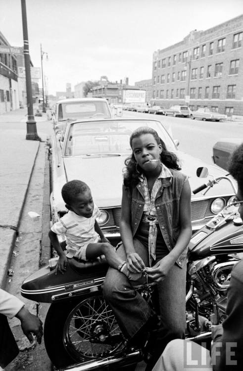 theconstantbuzz:  African American woman sitting on a motorcycle w. her child, part of the growing numbers of black motorcycle enthusiasts– circa 1971.