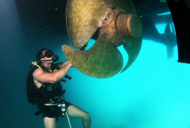 Navy Diver 3rd Class Bryan Myers maneuvers around a ships propeller looking for an inert training explosive by Official U.S. Navy Imagery on Flickr.