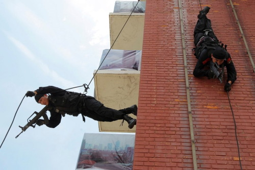 Paramilitary police in Shanghai rappel down a building during antiterrorism drill. New York Times: Pictures of the Day.