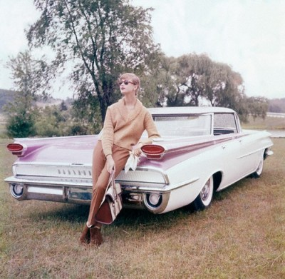 theniftyfifties:  Model wearing caramel knit fashions by a '59 Oldsmobile.