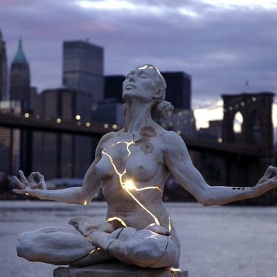 "poorartists:  Paige Bradley created one of the most striking sculptures I've seen in recent times. Her masterpiece, entitled Expansion, is a beautiful woman seeking inner piece but fractured and bleeding with light. ""From the moment we are born, the world tends to have a container already built for us to fit inside: a social security number, a gender, a race, a profession,"" says Bradley. ""I ponder if we are more defined by the container we are in than what we are inside. Would we recognize ourselves if we could expand beyond our bodies?"""