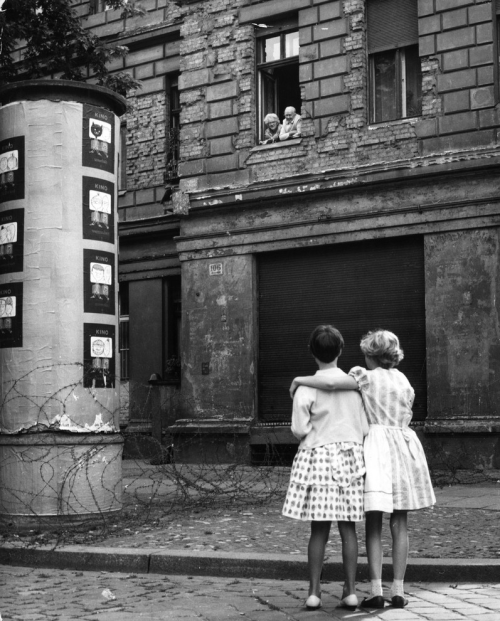 demons:  Two young girls in a West Germans street chat with their grandparents in the window of their home in the Eastern sector, separated only by a barbed wire barricade. It was a common occurrence for families, who had once only lived on the opposite side of the street from one another, to become separated by the ever growing Berlin Wall.