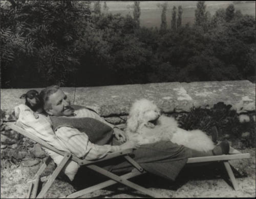 Gertrude Stein in 1934 with her dogs Pepe (acting as pillow) and Basket.