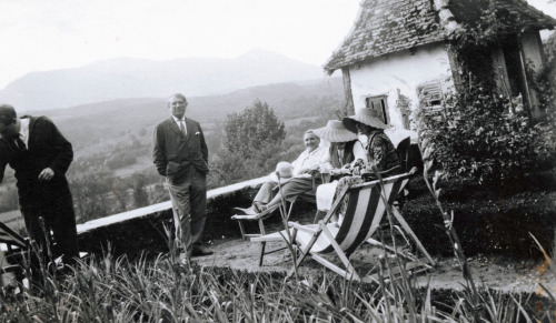 Gertrude Stein (hat on knee) with Pablo Picasso, standing, at Bilignin. Alice B. Toklas is at the right in the patterned dress and, I think, an enviable garden hat.