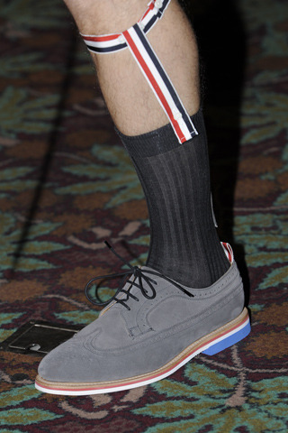 Thom Browne longwings with tri-colored sole (via GQ) — Earlier today goingoutgoingin replied to my earlier comment on a pair of Thom Browne longwings, in which I praised the tri-colored pulltab, which also doubles as a branding device for Thom Browne's line. He pointed out that I'd railed against branding on clothing and that perhaps liking a shoe for such branding is perhaps hypocritical, which is a fair point to bring up. In that same post on branding, I did mention that I liked Thom Browne's version of branding, as I thought it actually did something that wasn't tacky and played well with the clothes in how it was incorporated. On another level, I do like it simply because it can be used to echo other elements in your wardrobe in a place where you typically wouldn't involve color (your shoes). I'm a fan of Browne's colors that he uses, neutrals with red/white/blue. And while I think that his clothes and runway shows aren't anything I'd ever wear, I do find his accessories to be something that a lot of people could use and incorporate into their wardrobe easily — if you're someone who wears those colors quite a bit as I've been tending to do. I see Browne's stripes as more a signature of his brand than a logo, which might be splitting hairs in definitions, but I think that perhaps it's something worth differentiating. If you see a pair of shoes with brightly colored EVA soles, then you most likely know it's from Mark McNairy (or perhaps Jil Sander if the shoe's black). Is that a form of branding or a signature styling? Or both? Would I ever buy Browne's shoes at full retail for the express purpose of getting that pulltab? No. At a discount price comparable to another longwing that I perhaps had my eye on? Much more likely. It's more so a detail I enjoy as part of the whole shoe, not the fact I want to wear something designed by Browne to show it off, but I hardly think it's worth a premium price.