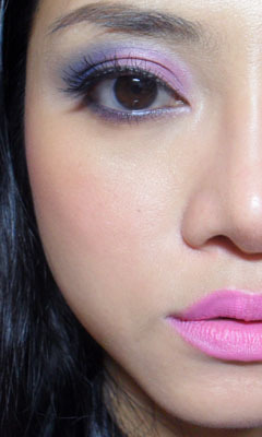 Stormy: Violet and Navy Eye with Matte Pink Lips (Revlon Stormy Pink) —- Been away on a work trip, and took the chance to stock up on some Revlon goodies at the Dutyfree Shops. (Haul details in another post.) One of the lipsticks I got was Revlon's Stormy Pink Matte Lipstick, and I have to say this is one of the most gorgeous pinks I have seen in a long while, although the texture and opacity does leave something to be desired in my opinion.  (And I thought I finally found a drugstore dupe for MAC Pink Nouveau…) —- Step 1: Apply a medium satin/matte purple over the inner 3/4 of the lids. I used a soft purple from the 88 palette.  —- Step 2: Using a matte navy blue, blend into the outer corners and up slightly along the hollows of the sockets. I chose Revlon Matte in Riviera Blue. The shadow will blend into an indigo or blue-violet as it hits the original purple.   —- Step 3: With a navy liner, line the water line and upper lash line. I like MAC Blooz for this, but most drugstore brands have a pearlescent navy that will do just as well.  —- Step 4: Apply black mascara or black wispy lashes to complete the look.  —- Cheeks and Lips: I used a hot pink blush (NYX Pinky) high along the cheekbones, and then a cool-toned medium pink from Revlon (Stormy Pink*) on the lips. *To get the sheer, patchy, cakey texture to work, I filled in my lips first with NYX Dolly Pink liner, and then ran a tiny touch of non-shiny lip balm over it. This creates a smooth base, which helps the lipstick to adhere and look more opaque.