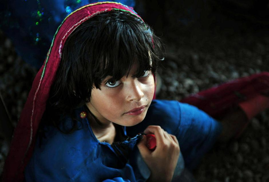 A young Afghan refugee poses at The United Nations High Commissioner for Refugees (UNHCR) registration centre on the outskirts of Peshawar on June 20, 2011, prior to returning to her home country Afghanistan, after fleeing civil war and Taliban rule. Pakistan is host a refugee population of 1.9 million.