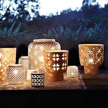 Perforated white porcelain hurricanes cast a romantic glow when lit from within. via West Elm.