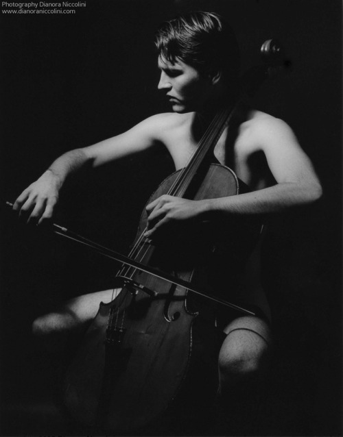 A black and white image of a naked slender man playing the cello