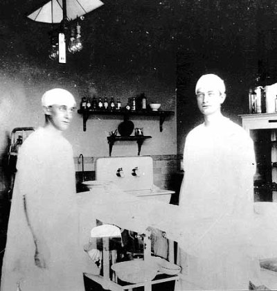 Drs. Charles Horace Mayo and William James Mayo in operating room in the first operating room at St. Mary's Hospital, Rochester, MN. 1904.  The brothers Mayo founded the Mayo Clinic in Rochester in 1919, from the private practice they once shared with their father. They brought on six other doctors that they knew well, and this group of eight practitioners was the first in the world to emphasize specialization (especially ophthalmology and surgery of the thyroid and nervous system) and an integrated group practice, where you could still go to one place to be treated, but different doctors had different specializations. In 1964, a 5-cent postage stamp was released with the brothers' likenesses on it.