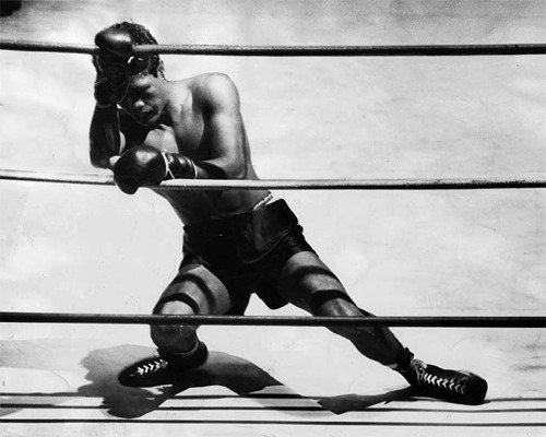 "latimes:  ""Oct. 31, 1950: Bernard 'Big Duke' Docusen hangs on to the ropes at end of the second round after taking several hard punches from John L. Davis. The referee halted the bout on a technical knockout immediately after third round started."""
