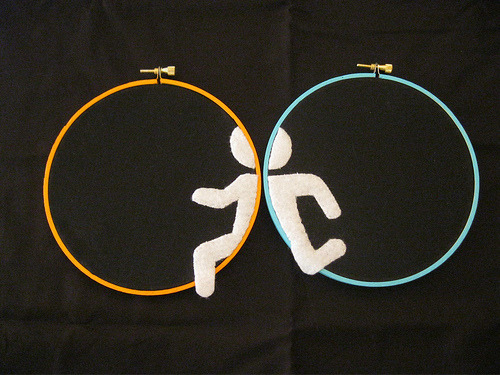 "Crafter Trouble T not only stitched these clever Portal 2 needlework hoops for her husband as a Father's Day gift, but also gave him this rad looking ""Binary Man"". That's some neat gifts.  Man there's been a lot of neat Portal fan work recently! Chalk drawings and pool parties included. Portal Hoops via Neatorama"