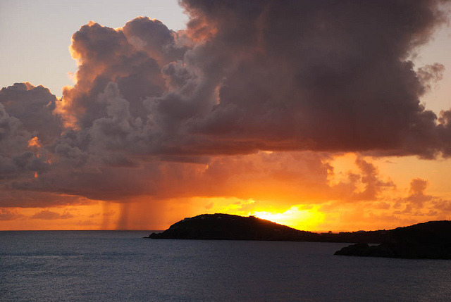 Storming in the sunset on Flickr. Docked on a cruise ship in the Caribbean, it was the first time I had seen it rain off in the distance while staying dry. Seeing this made me think more and more than rain is magic, How does it just spill out like that over there and not on top of me? And how is the sun still out if its raining?