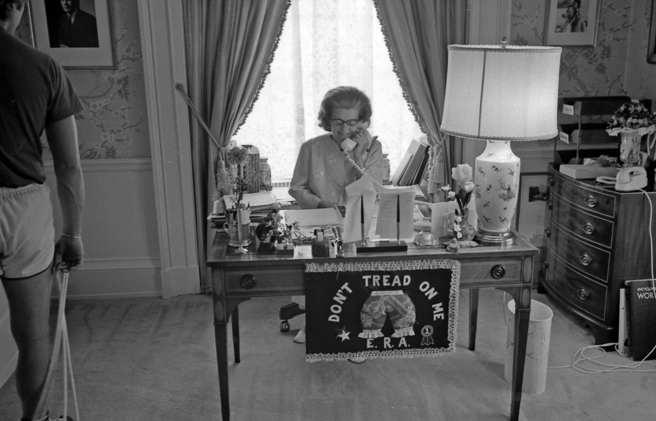 "ourpresidents:  Meanwhile in the East Wing… First Lady Betty Ford works at her desk, where a ""Don't Tread on Me"" Equal Rights Amendment doormat hangs.  June 30, 1975. -from the Ford Presidential Library and Museum"