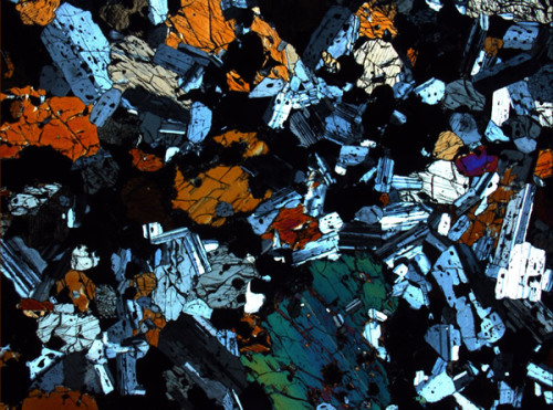 Photomicrograph of a section of gabbro (via Istituto Nazionale di Geofisica e Vulcanologia)  Gabbro refers to a large group of dark, coarse-grained, intrusive mafic igneous rocks chemically equivalent to basalt. The rocks are plutonic, formed when molten magma is trapped beneath the Earth's surface and cools into a crystalline mass. (via W.)
