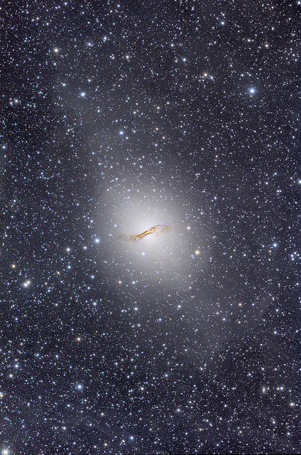 "spacettf:  Centaurus A Ultra Deep Field by strongmanmike2002 on Flickr.Via Flickr: Date Taken: May 2008 Location: ""Wiruna"" - dark sky site of the Astronomical Society of New South Wales. Telescope: Astrophysics Starfire 152mm EDF F7.5 APO This image may well be the deepest colour image ever displayed of the full extent of Centaurus A and its immediate surrounds. The image reveals the full visual dynamic range of this incredible and unusual southern galaxy, from its intense bright core bisected by an intricate and detailed dust lane right out to the very faintest extremities of the enormous galactic halo shining feebly at a tiny fraction of the natural sky background. The image indicates that the main circular galaxy halo extends out some 70 000 light years from the galaxy core while faint outer extensions perpendicular to the dust lane in both directions, take the visible extent of the galaxy out to an apparent 150 000 light years from the core or a diameter of 300 000 light years that covers some 84' X 45' of our night sky. Subtle mottled bright and dark patches within the huge galactic halo are hallmarks of a recently discovered complex system of stellar ""shells"" caused by an ancient collision with another galaxy. Showing up all over the field and looking like a patchy milky substance, is a layer of extremely faint (less than 27mag/squ arc sec) intervening Milky Way Cirrus dust. This dust hovers above the plane of our own Milky Way Galaxy and shines by the collective light of the stars in the Milky Way as a whole. A closer inspection also reveals many globular clusters in the halo of the galaxy as well as thousands of very distant galaxies of all shapes and sizes in the background. Michael Sidonio  m.sidonio@bigpond.com"