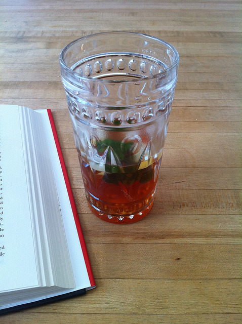 "It's been more than a year since I last inundated you all with photos of glasses of iced tea! Did you miss it? I did. I spent a summer while I was in college working for Tealuxe in Boston. I made a lot of iced tea in mass quantities.* I'd scoop the tea leaves into long paper envelopes about the size of postcards, staple them together, drop them into a big metal double-walled drum with a spigot at the bottom, fill it halfway with boiling water, and then set a timer for it to steep. When the timer went off, I'd fill the rest of the drum with ice.** The key was that you made the tea twice as strong and steeped it twice as long as you would for hot tea. The other key was that you tried to avoid accidentally spilling the drum of boiling water on yourself and necessitating a trip to the emergency room. This is a process that's pretty easy to translate to home-cooking quantities, and there's quite a bit less risk of really painful burns. I have a six-cup teapot and a more than 12-cup glass pitcher. You do not want to pour boiling water that you will then quickly cool into a glass pitcher (unless you want the glass to shatter all over, as it did frequently when someone new decided that they could pour iced tea into glasses still hot from the dishwasher). And I want more than six cups of iced tea. However, you can make the twice-as-strong, twice-as-long tea in the teapot, cool it a little, and then pour it into the pitcher to cool it the rest of the way. I would recommend this also if you only have a plastic pitcher, since there's something about pouring boiling water into plastic that makes me uncomfortable. Pour boiling water over 7 or 8 teabags of black tea (I used half decaf English Breakfast and half regular English Breakfast) in a six cup teapot. Cover and set a timer for seven or so minutes (black tea would normally steep for 3 - 5 minutes). Remove tea bags and stir in anywhere from 1 tablespoon to 1/4 cup of honey (I generally use about 2 tablespoons). Add a handful of ice. Stir to dissolve. Pour some of the tea carefully into your larger pitcher, add more ice to the remaining tea in the teapot, stir, and pour the remaining tea into the pitcher. Add at least one full tray of ice to the pitcher, possibly more. If you have it, crumple up a sprig of mint and toss it in. It's good for a few days in the fridge.  Here's a picture from my office so you can see exactly how messy things have gotten in the past year. * I also mastered a facial expression that communicated 80% ""I am a pleasant and accommodating food service professional that values you as a customer and fellow human being"" and 20% withering disdain. ** If you go into a tea shop, and instead of having a selection of two to four iced tea varieties available, they tell you that they can ""make iced tea from any of their teas!"" that means you're going to be waiting basically forever for your iced tea. If there's a line, and you ask them to make you some custom iced tea, you will probably get a look that's at least 40% withering disdain."