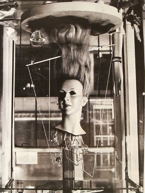 The Dew Machine, 1937 by Roland Penrose  Hair had been an important theme for Roland Penrose before he met Lee Miller when he created a Surrealist object titled The Dew Machine (destroyed in the war) made from the head he sawed off a mannequin . He had a wig made of long blonde straight hair, added false eyelashes, and completed her transformation to life by painting the eyes, lips and flesh tones. The head, elegant but banal, hovers upside down above a baseboard and the kind of funnels used by chemists are inserted into the neck, filled with coloured beads. Thin strings connect the funnels to a stick that passes through the hair that caresses the baseboard. A further wine glass shaped apparatus completes the object, and strengthens the conjunction between the forces of arcane magic and the magic of science. It is easy to imagine the object scaled to a gigantic size, the funnels loaded with mysterious substances feeding the hair that softly trails across the countryside wherever dew is needed .  from MONDOBLOGO [caption found accompanying this work]