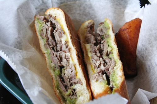 """The El Caney: chopped slow roasted pork, avocado, cheese, a touch of mustard, and our signature mojo sauce."""