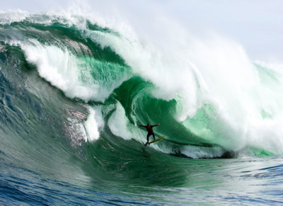 "On Our Ultimate Bucket List: Surf Big Waves at Shipsterns Bluff, Tasmania, Australia On the far southern coast of Tasmania, jutting into one of the Earth's most unpredictable and tempestuous seas, lies a point break so remote and isolated it's reachable only by boat or an hour-long wilderness trek. This is Shipsterns Bluff, a cold and dangerously unpredictable break where waves start crashing at eight feet (two meters) but can top 20 feet (six meters). The waves' characteristic steps trip even expert surfers–recently such as Kelly Slater and Ryan Hipwood (pictured)–and swing perilously close to rock fields, but the rush of lassoing the goliath of all waves beneath the coast's dwarfing black cliffs keeps surfers returning. ""The scariest part is seeing the wave and committing to catching it,"" says local surfer Charles Ward. ""But once committed, it all tends to feel surreal and I forget about everything except what's right in front of me."" Photograph by Stuart Gibson"