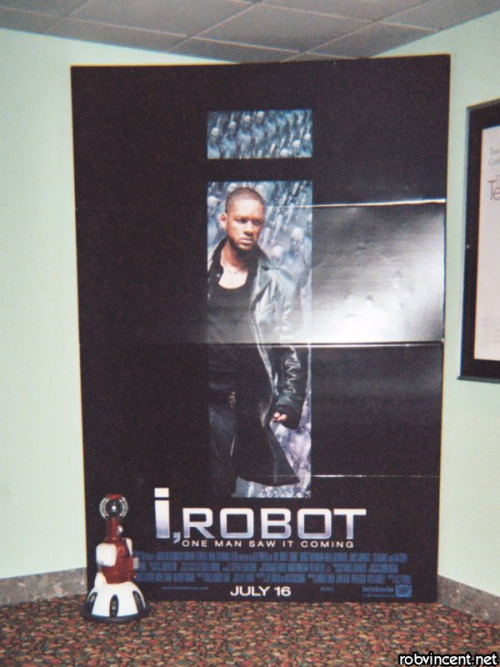 My homemade Tom Servo hanging out at the movies in 2004.  This display seemed to catch his interest for some reason. He's a totally functional puppet, built out of most of the same parts as the MST3K crew used (or, where unavailable, fan-made replicas of same.)  I'll put up some clearer pics of him soonish.