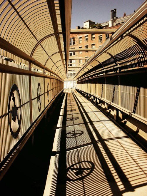 "nythroughthelens:  Converging lines. Tribeca, New York City. Buy ""Convergence"" Posters and Prints here, View my store, email me, or ask for help. I have been shuffling things around on my computer network to make room for newer files (photo files take up so much space!) and I came across this photo that I took this past October. I love the converging lines in this image produced by the shadows of the footbridge."