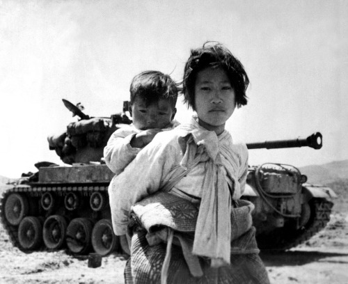 shallowrights:  With her brother on her back a war weary Korean girl tiredly trudges by a stalled tank, at Haengju, Korea. June 9, 1951.
