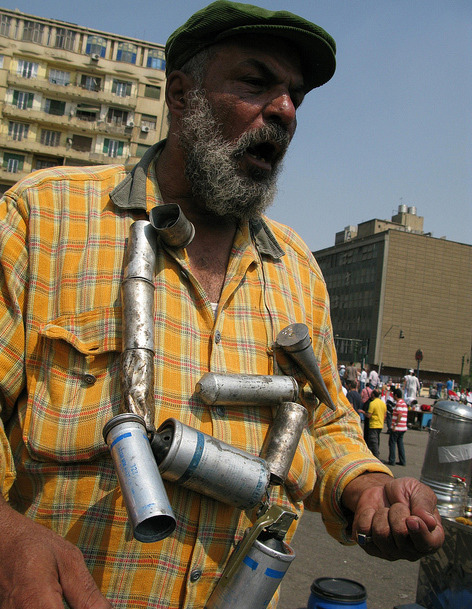 Man wears a necklace made of spent tear gas canisters in Tahrir Square, Egypt. Photo by Andy Carvin posted on Flickr.