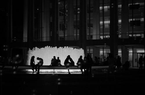 "The Lincoln Center Fountain at night adorned by lovers and bubbles. Upper West Side, New York City.  Buy ""New York City Romance"" Posters and Prints here, View my store, email me, or ask for help.  Lincoln Center's iconic fountain opened in 1964. It's played a tiny role in several films throughout the years like The Producers, Moonstruck and Sweet Home Alabama. The cast of Glee also filmed there recently.  The fountain was revitalized in 2010 and it's now better than ever:  ""The fountain has three hundred and seventeen computerized jets, which are arranged in two rings around the perimeter of the fountain, with radial arms leading to a central circular mass of more jets. A WET choreographer named Peter Kopik designed a daytime and an evening program for the fountain. The new fountain débuted on October 1st 2010, and the daytime program has been running since then. When the jets are all on, they produce a mighty column of water that slowly rises on a height of twelve feet. When the column is at its greatest height, there are four hundred and seventy-five gallons of water in the air. Especially after dark, people are drawn to the column of water, mesmerized by the two hundred and seventy-two L.E.D. lights that make the water glow white. "" Source"