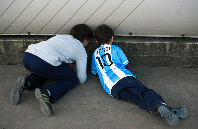 n8thehuman:  Two children peep through a fence trying to see Argentine footballers at the hotel where Argentina's national team is staying.