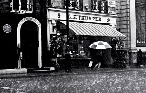 "Battling through the rain, Curzon Street, Mayfair, London, England ""On Curzon Street in London's Mayfair last year a heavy rainstorm appeared from nowhere. The streets cleared within seconds; doorways filled with unprepared pedestrians, including me. We all marvelled at and discussed the rain apart from the lady with her umbrella who battled through. Thirty seconds later the weather completely cleared and the streets filled up again as we left our temporary shelters. I quickly took this before the rain obscured my lens"" By: William McCracken"