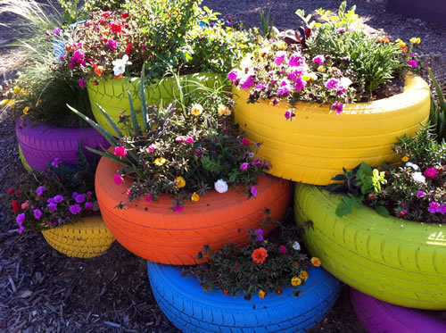 What a great idea for school and community gardens: brightly painted tires, filled with dirt and stacked together as planter beds.