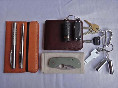 submitted by Scott P.  Heav(ier) duty EDC, usually carried in a small shoulder bag: Guildhall pocket notebook (much better quality than Moleskine imho), in a plain leather cover.Stainless Embassy pen, stainless Maxmadco pen.Undyed cotton handkerchief.Spyderco Leaf Storm.Saddleback Leather medium bifold wallet.Keychain and tools: Muyshondt Aeon, Leatherman Squirt PS4, and Imakey, and 2 stainless storage fobs.  Editor's Note: Nice setup… with an EDC bag I see you can manage to carry a nice notebook, some heavy duty pens, and a Saddleback bifold (which aren't the slimmest to carry I'd imagine, but here it should carry fine and last forever). Good choice on the primary bladetoo. Despite it being one of my older knives, my Leafstorm's in my pocket every day (still can't think of a suitable replacement for myself…). I like the pairing of the Aeon and the Squirt, as well as how your keys are modular for ease of access and customization. One concern I have is the two pill-fobs on one McGizmo clip situation — they seem to dangle awkwardly (which again, might not matter if it's in a bag). I can't tell from the photo what size clips those are too, but I generally avoid the smaller clips because they tend to easily unclip gear, in my experience. Looking good overall, thanks for sharing.