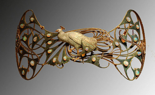 "René Lalique (1860-1945)France, c.1898-1900 Gold, enamel, opals, diamonds ""Of all the animals reproduced in the work of Lalique, the peacock is perhaps regarded as the most emblematic of the spirit of Art Nouveau, and it is a recurring theme in the artist's work, whether isolated as here or in pairs in other jewels. The theme is again very representative of Symbolist painting, as a symbol par excellence of natural beauty in all its splendour. This pectoral is made up of an enormous, articulated peacock in enamelled gold in tones of blue and green simulating the feathers of the bird which have small cabochon-oval opals set here and there. Sinuous movement of the feathers in the tail, turned to the left, is enriched by a balanced composition of diamonds, of various sizes, that finish off the piece on both sides."""
