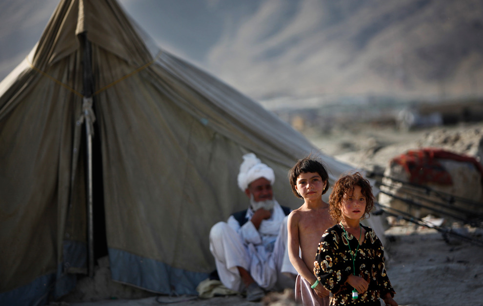 Afghans near a makeshift tent at a camp for refugees in Kabul, Afghanistan, June 20, 2011