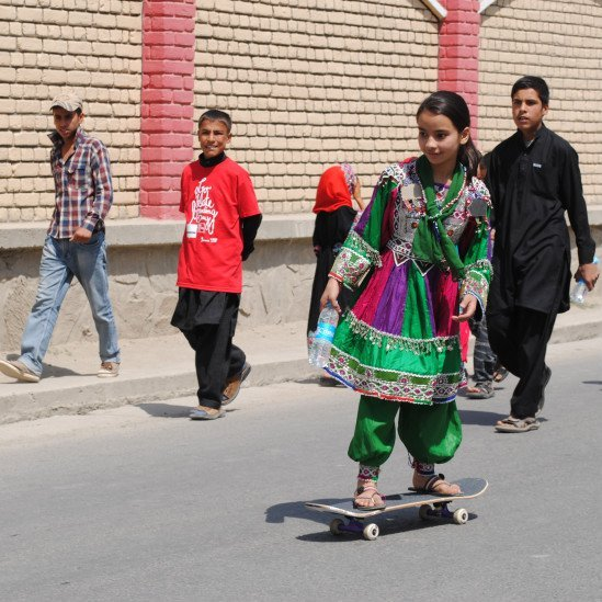 Afghan girl skating wearing traditional dress.