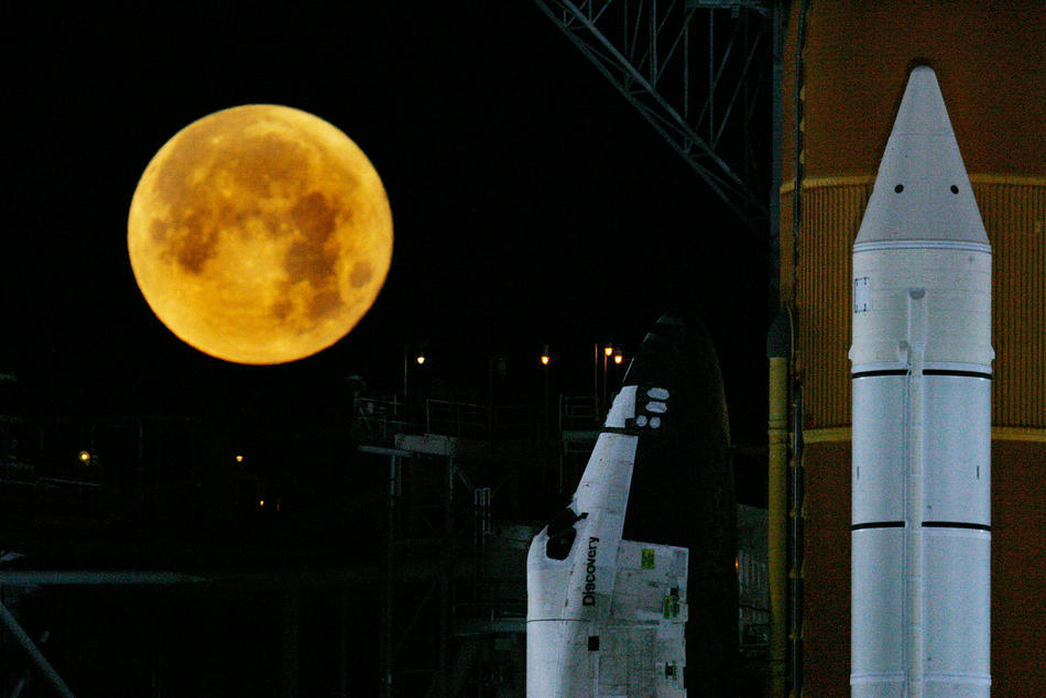 The moon is seen near the Space Shuttle Discovery STS-119 as it sits on the launch pad while it is prepared for launch March 11, 2009 in Cape Canaveral, Florida. The Discovery is being prepared for the scheduled launch date of March 11, 2009 on a mission to the international space station. (Photo by Eliot J. Schechter/Getty Images)